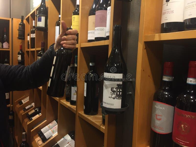 Köpa en flaska av vin i supermarket fotografering för bildbyråer
