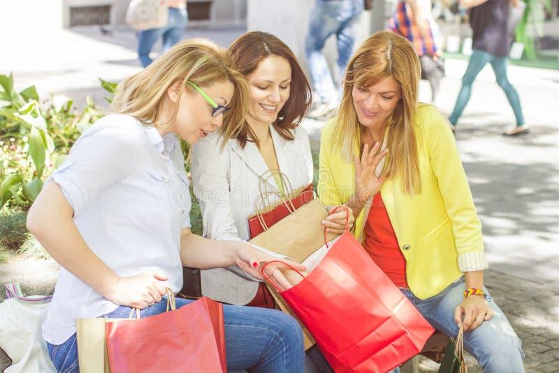 Köpa för vänner för lycklig shopping som kvinnligt är utomhus- arkivfoton