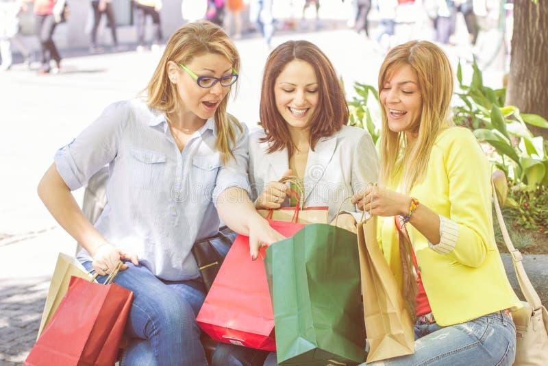 Köpa för vänner för lycklig shopping som kvinnligt är utomhus- arkivbilder