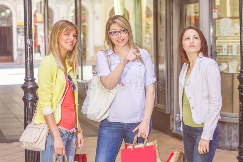 Köpa för vänner för shopping som kvinnligt är utomhus- royaltyfria foton