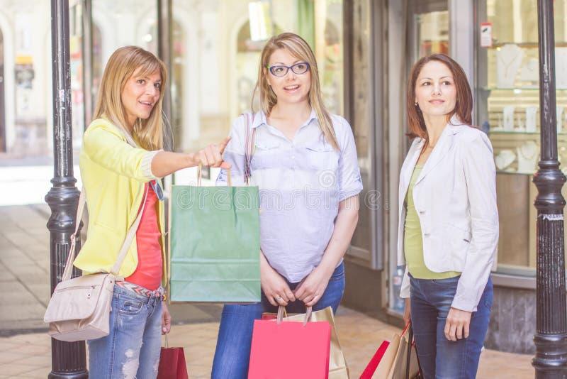 Köpa för vänner för shopping som kvinnligt är utomhus- royaltyfri foto