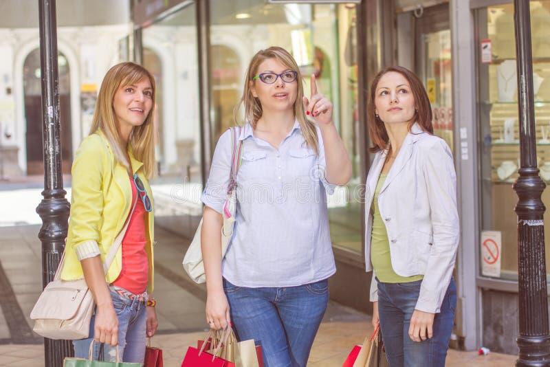 Köpa för vänner för shopping som kvinnligt är utomhus- royaltyfria bilder