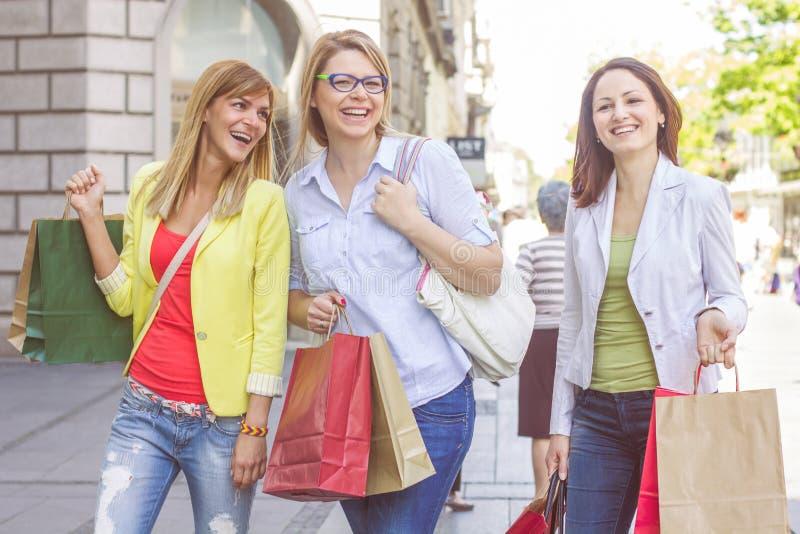 Köpa för vänner för shopping som kvinnligt är utomhus- fotografering för bildbyråer