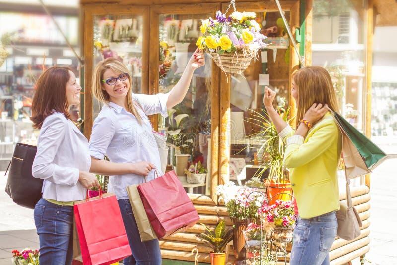 Köpa för vänner för shopping som kvinnligt är utomhus- royaltyfri bild