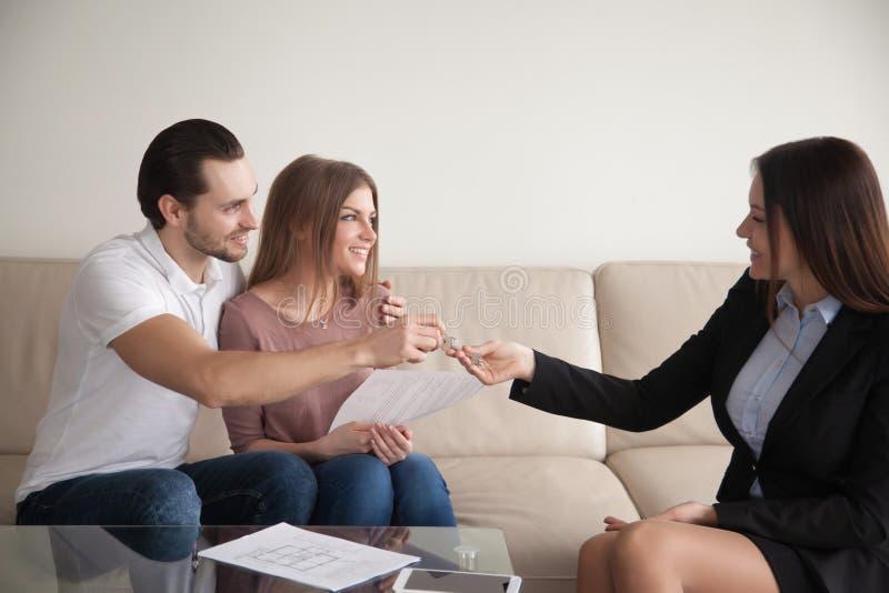köpa home Unga lyckliga par som får tangenter av egen lägenhet fotografering för bildbyråer