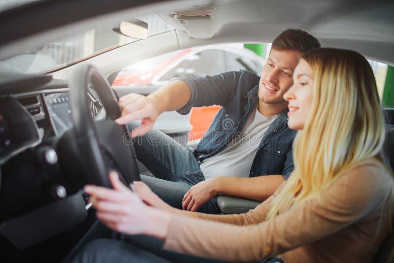 Köpande första elbil för ung familj i visningslokalen Attraktiva le par som ser knappar på styrninghjulet arkivfoto
