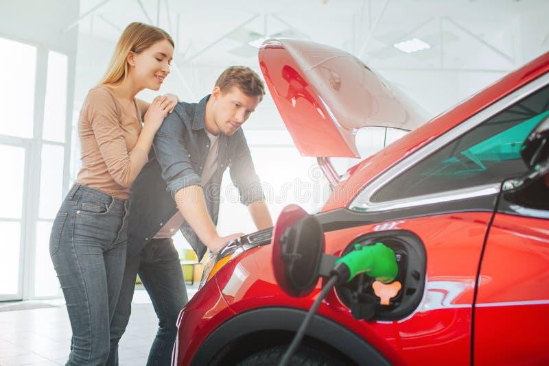 Köpande första elbil för ung familj i visningslokalen Attraktiva par som ser under denvänskapsmatch bilhuven elkraft royaltyfria foton