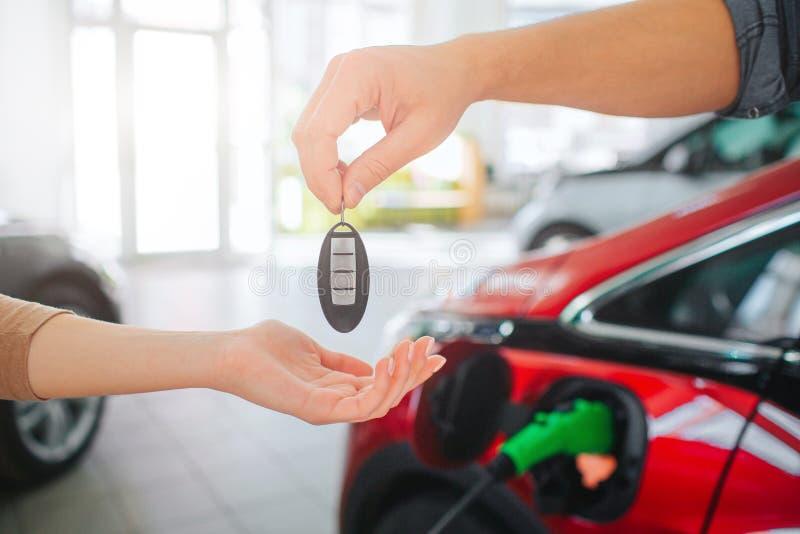 Köpande första elbil för ung familj i visningslokalen Närbild av den manliga handen som ger biltangent till den kvinnliga handen  arkivfoton