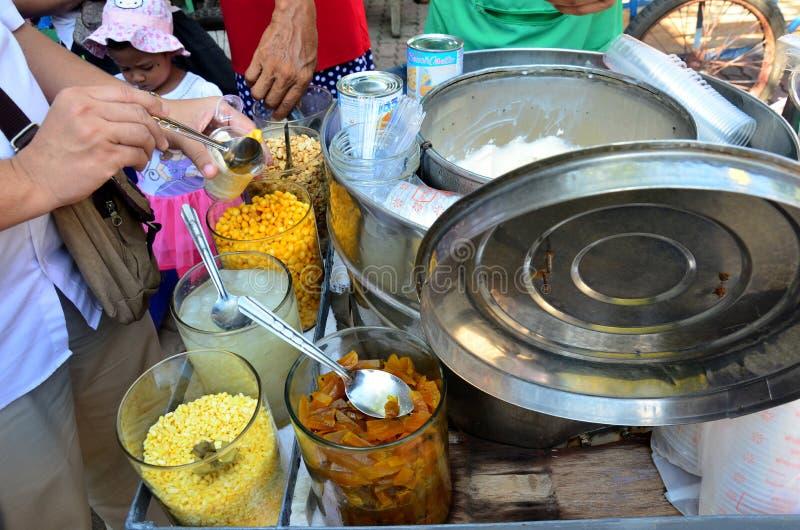 Köpande kokosnötglass för folk och vald toppning royaltyfri foto