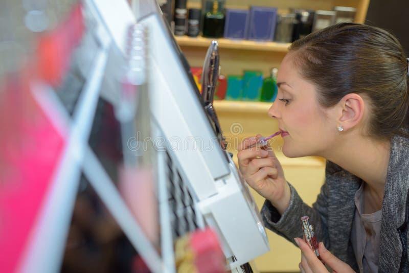 Köpande läppstift för härlig ung kvinna royaltyfri foto