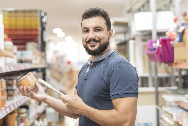 Köpande målarfärger för skäggig man i supermarket och hantverklager fotografering för bildbyråer