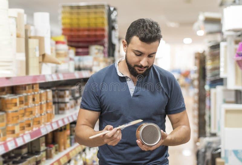 Köpande målarfärger för skäggig man i supermarket och hantverklager arkivbild