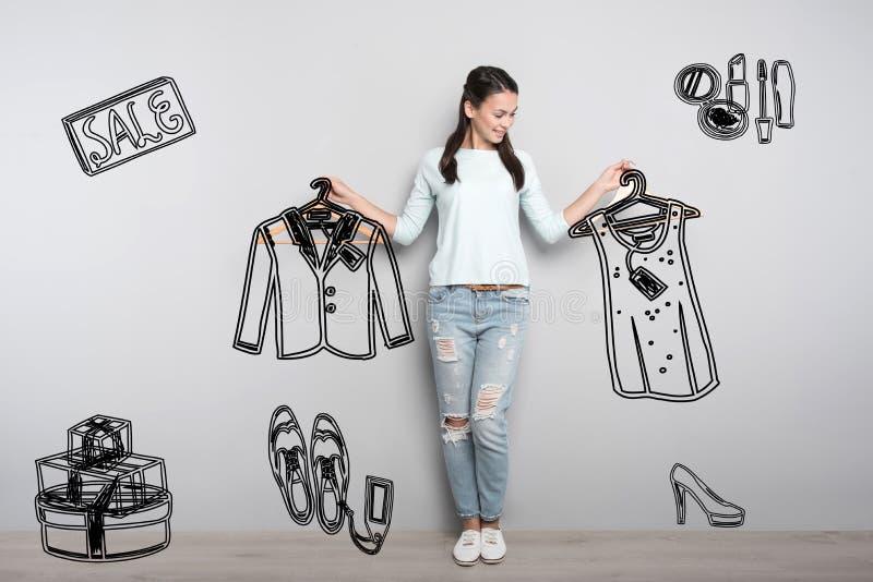 Köpandekläder för ung person med stor rabatt och se glat arkivbilder