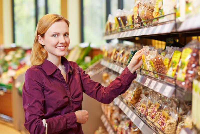 Köpandepåse för ung kvinna av muttrar i supermarket arkivbilder