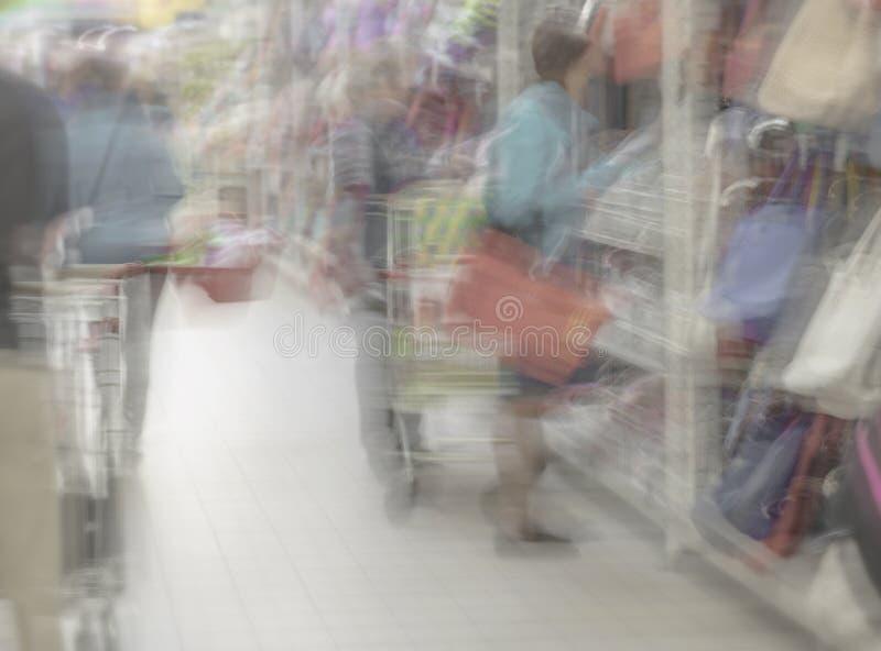 Köpcentret shoppar gallerialagret Kvinna i supermarket med shoppingkorgen, detaljhandel Abstrakt defocused suddigt för rörelse royaltyfri foto
