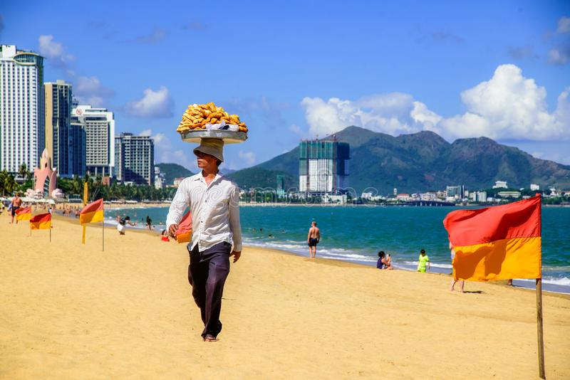 Köpmän säljer lokal mat till turister på en strand av havet och bergen royaltyfria bilder
