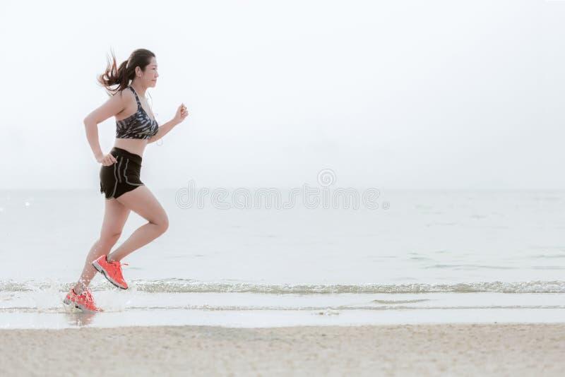 Köra för löparefot som är utomhus- på stranden Asiatisk kondition och sportig kvinna som kör för sunt royaltyfri foto