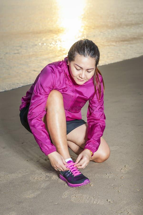 Köra och jogga öva begrepp Kvinnaband snör åt, innan det utbildar på stranden Bärande sportskor för asiatisk flicka royaltyfri bild