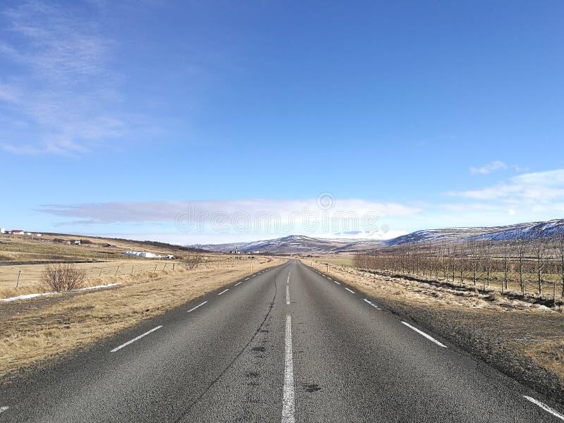 Köra på tomt öppna asfaltvägen in mot område av berg som täckas i snö på solig dag för blå himmel, affärsframgång och vägforw arkivfoton