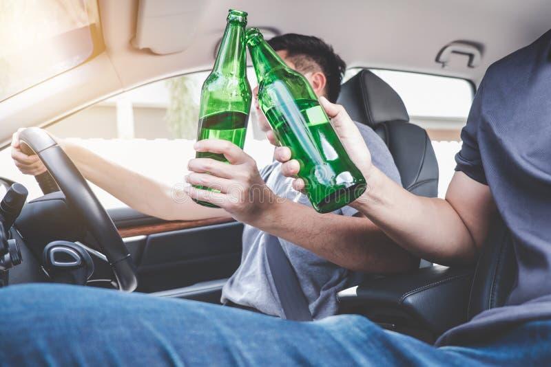 Köra under påverkan få in i olycka, två som den asiatiska mannen kör en bil med berusat en flaska av ölalkohol bak styrningen arkivbilder