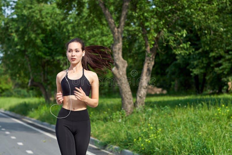 Körande asiatisk kvinna på körande spår Jogga f?r morgon Idrottsman nenutbildningen royaltyfria bilder