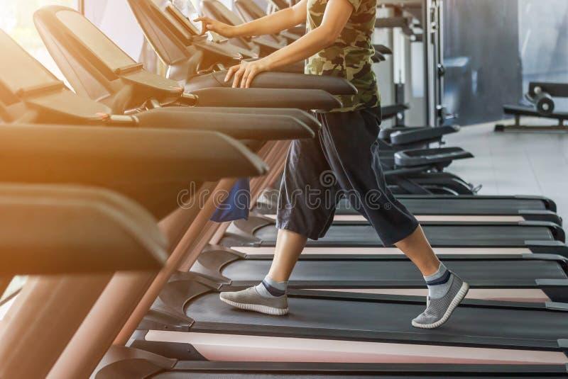 Körande genomkörare för sportig kvinnaövning på den spårande vård- övningen för trampkvarnutrustning för bodybuilding i modern ko royaltyfria bilder