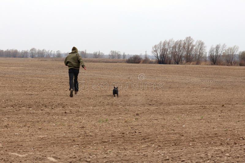 Körande grabb med en svart hund på ett plogat svart fält royaltyfria foton