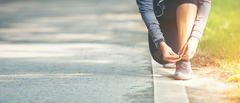 Körande kvinnaband snör åt av springskor, innan det joggar till och med vägen i genomkörarenaturen, parkerar, text för baner och  arkivfoton