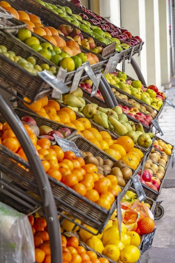 Körbe der Frucht stehend auf einem Regal vor einem Geschäft auf dem Bürgersteig lizenzfreie stockbilder