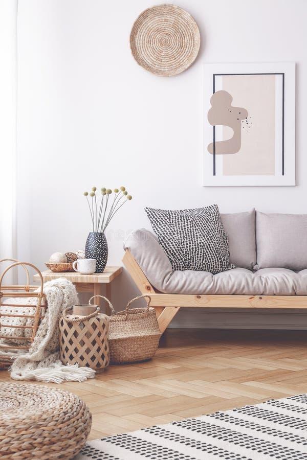 Körbe und Puff auf Bretterboden im Wohnzimmerinnenraum mit Plakat über grauem Sofa Reales Foto lizenzfreies stockfoto