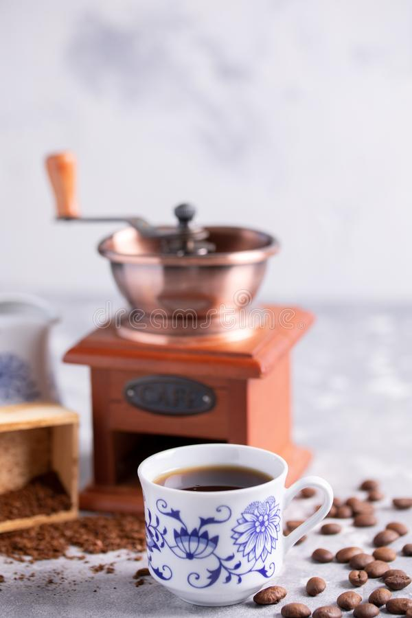 Körner des Kaffees fallen aus einer Weinlesekaffeemühle heraus Heißer schwarzer Kaffee in einem schönen Porzellan höhlen auf dem  lizenzfreie stockfotos