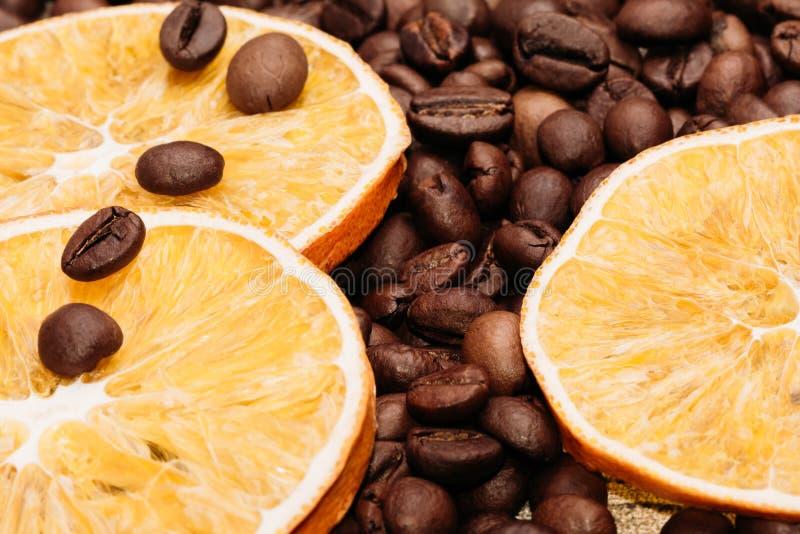 Körner des Kaffees mit getrockneter orange Nahaufnahme lizenzfreies stockbild