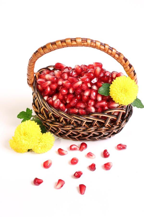 Körner eines Granatapfels, Blumen in einem Korb. lizenzfreies stockbild