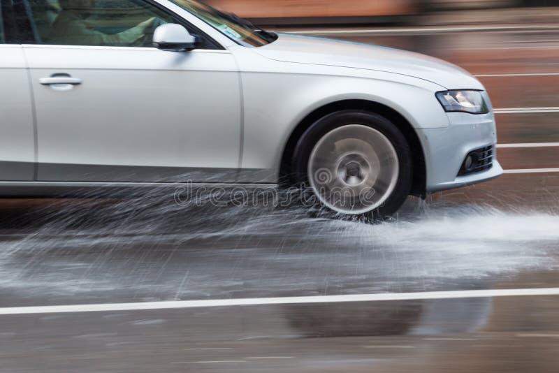Körning av bilen på en våt gata royaltyfria bilder