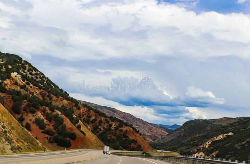 Körning av den krökta vägen till och med mountiansna med härlig blå molnig himmel och tunnelen i avståndet fotografering för bildbyråer