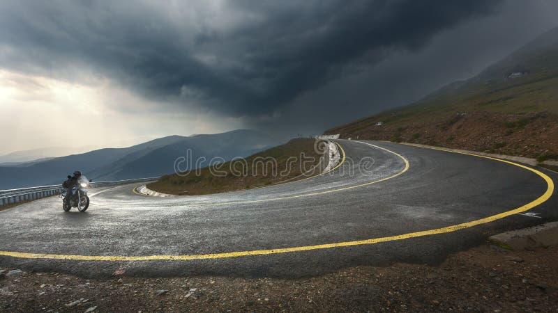 Körning av en motorcykel på den alpina huvudvägen in mot stormen royaltyfri fotografi
