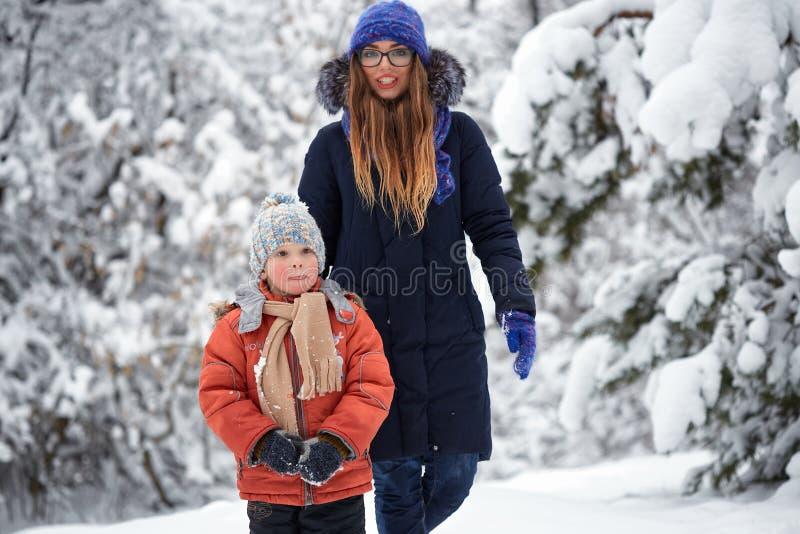 körning av rolig pulkavinter pojke med en flicka som går på en vinterväg royaltyfria bilder
