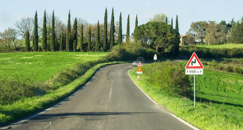 Körning av vägen böjer vägmärket som indikerar kurvan arkivbild