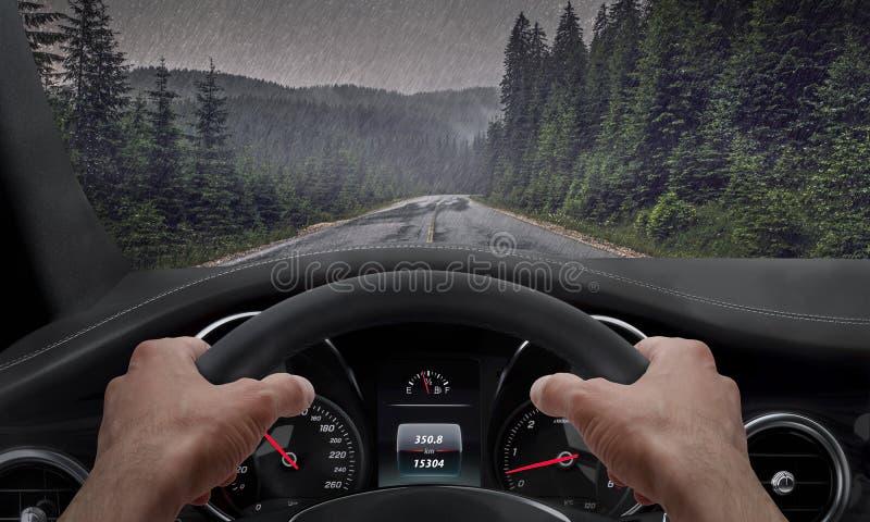 Körning i regnigt väder Sikt från chaufförvinkeln medan händer på hjulet Regn plaskad vindruta royaltyfri fotografi