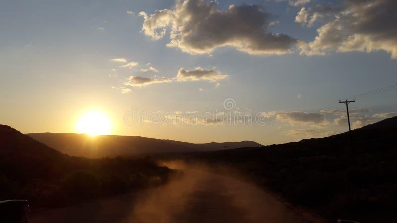 Körning i väg från solnedgången arkivfoto