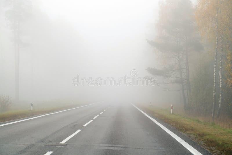 Körning på bygdvägen i dimma Illustration av faror av D arkivbilder
