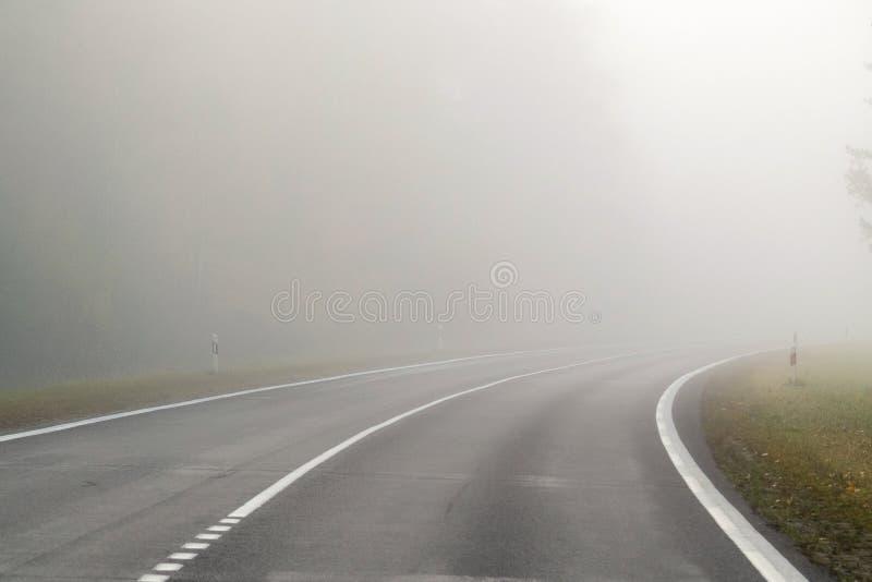 Körning på bygdvägen i dimma Illustration av faror av D fotografering för bildbyråer