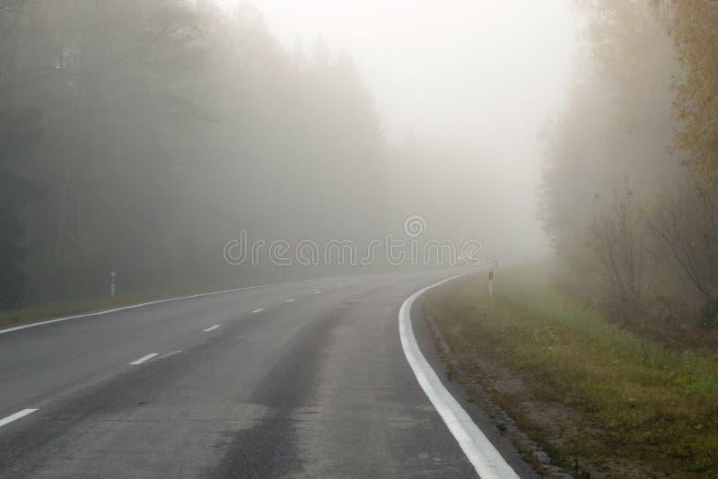 Körning på bygdvägen i dimma Illustration av faror av D royaltyfri foto