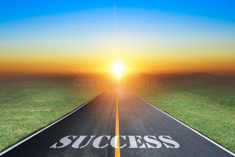 Körning på en tom asfaltväg in mot det inställningssolen och tecknet som som symboliserar framgång arkivfoton