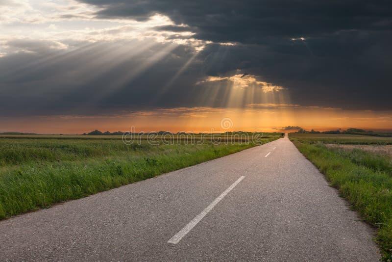 Körning på en tom landsväg på solnedgången fotografering för bildbyråer