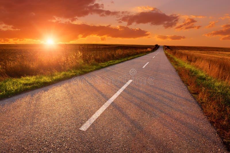 Körning på en tom väg på solnedgången royaltyfri bild