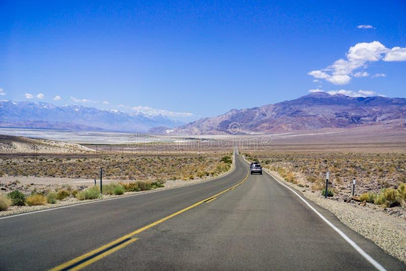 Körning på huvudvägen till och med Inyo County; Toppig bergskedja bergskedja med snöig maxima på vänstersidan; Kalifornien arkivbilder