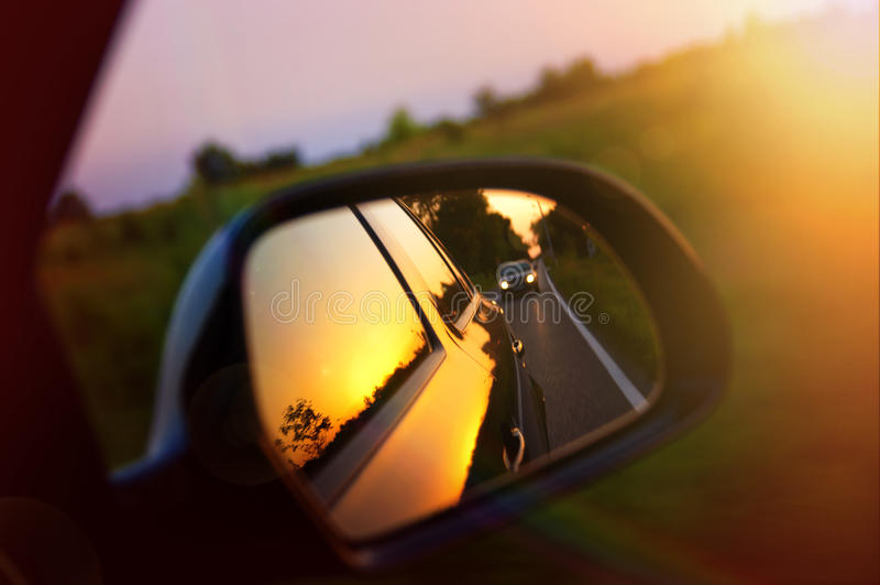 Körning på solnedgången - spegel för bakre sikt royaltyfri fotografi