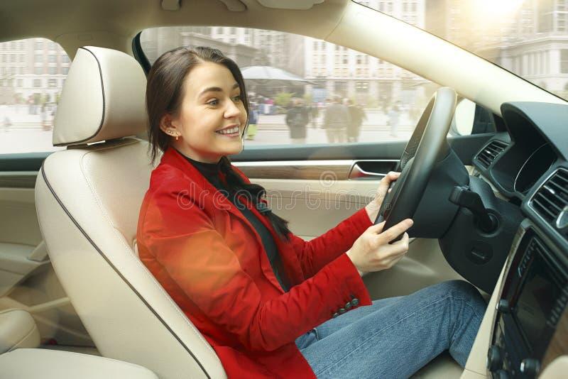 Körning runt om stad Ung attraktiv kvinna som kör en bil arkivfoton