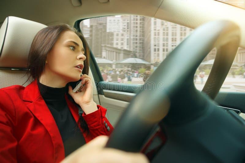 Körning runt om stad Ung attraktiv kvinna som kör en bil royaltyfri foto